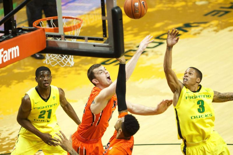 Beavers center Angus Brandt and Ducks guard Joseph Young (right) jump for a rebound.