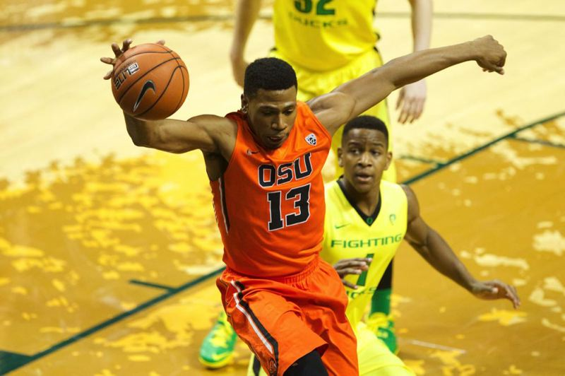 Beavers guard Langston Morris-Walker attempts to keep the ball inbound as Oregon guard Dominic Artis moves in on the play.