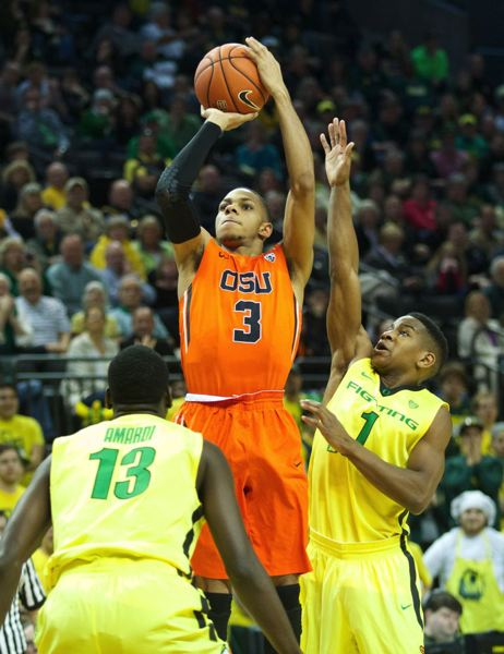 Hallice Cooke shoots over UO's Dominic Artis (right) and Ducks forward Richard Amardi.