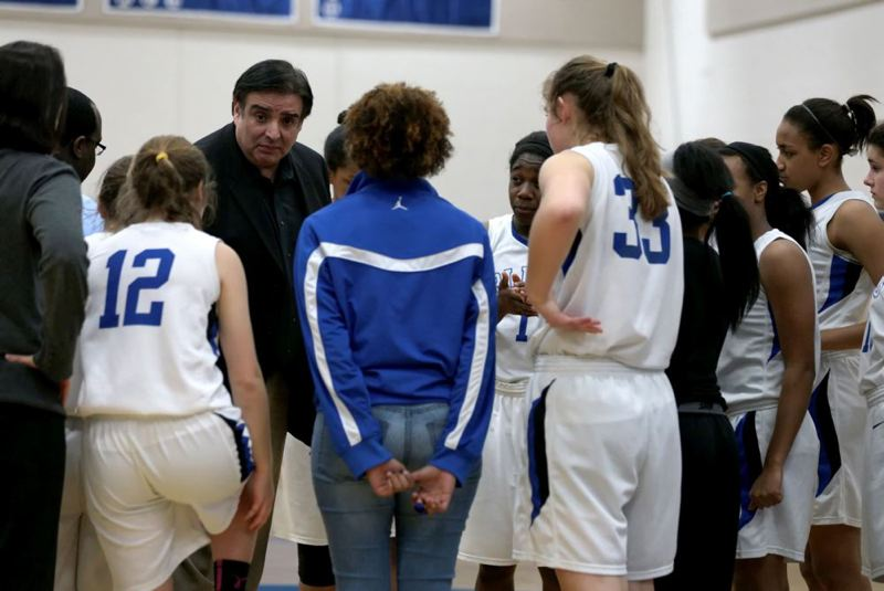 by: TRIBUNE PHOTO: JONATHAN HOUSE - St. Mary's Academy coach Art Rojas and the Blues huddle during a timeout en route to their 71-41 victory over Central Catholic.