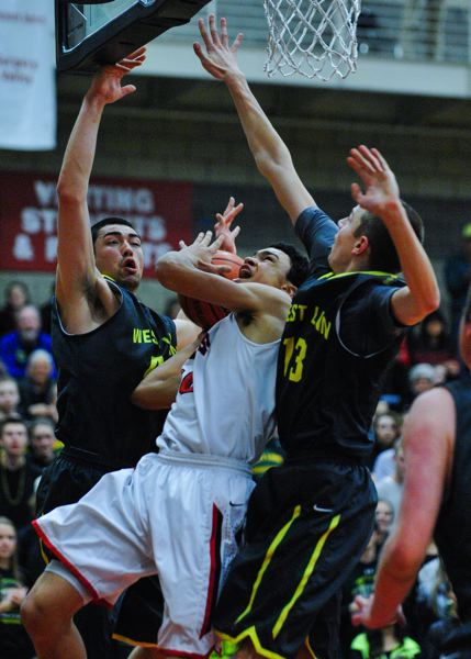 by: JOHN LARIVIERE - Clackamas junior Markus Golder gets hammered as he attempts to take the ball to the basket in last weeks game with West Linn.