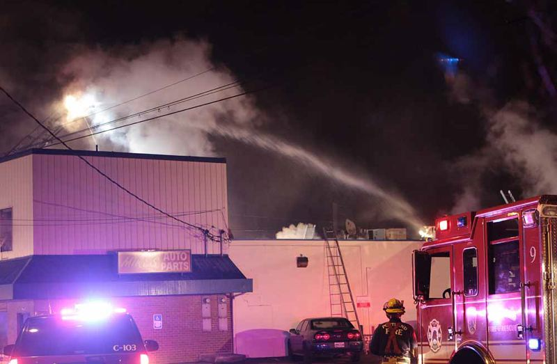 by: PAMPLIN MEDIA GROUP: DAVID ASHTON - Portland fire crews used powerful squirt trucks to bring a two-alarm fire under control Monday night at Mike's Auto Parts on Southeast 52nd Avenue. No one was injured, and residents of several apartments above the store were forced out of the building by the heavy smoke.