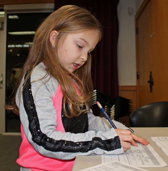 by: SPOKESMAN PHOTO:  KATE HOOTS - Reese Buchanan, a second-grader at Lowrie, fills out an application for a public library card of her own Feb. 13.