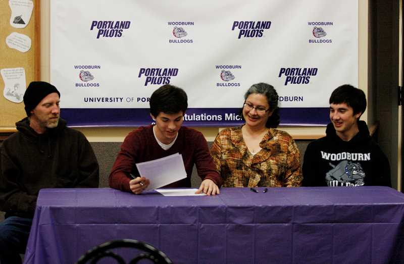 by: PAMPLIN MEDIA GROUP: PHIL HAWKINS - Michael Hobson signs his letter-of-intent to play with the University of Portland Pilots. He is flanked by his parents, Tom and Annette, and younger brother Brandon.