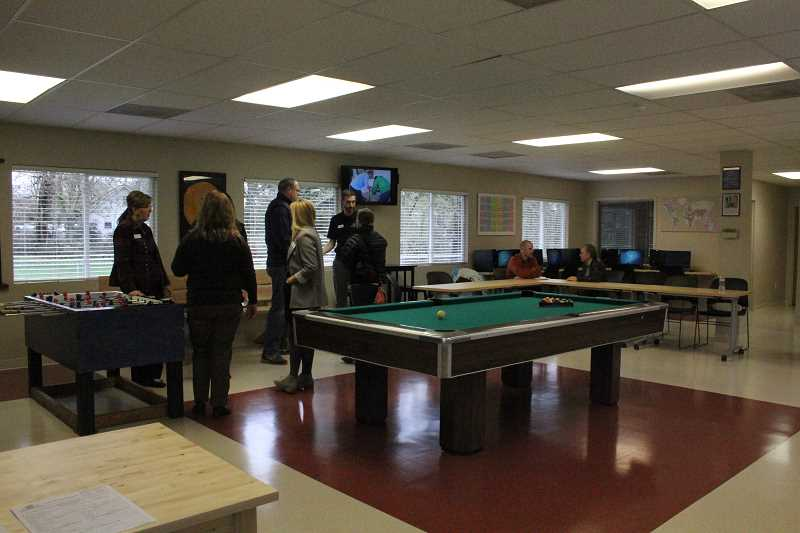 by: LINDSAY KEEFER - Community members gather in the newly remodeled space at Woodburn Boys & Girls Club.