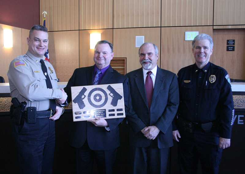 Sheriff Jim Adkins, left, accepte the winners' plaque for his department from Richard Ladeby of Deer Ridge Correctional Institution, DRCI Administrator Rick Angelozzzi, and Madras Police Chief Tom Adams.