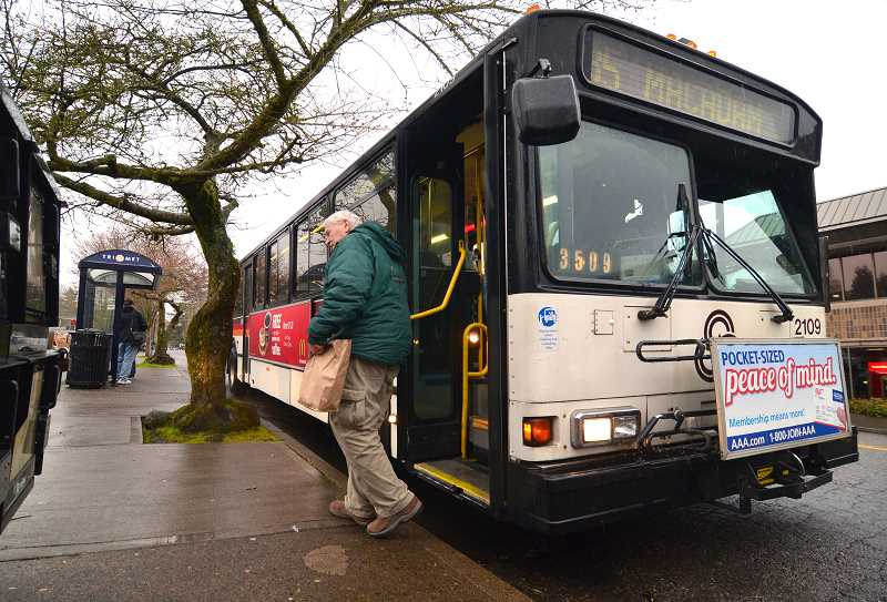 by: REVIEW FILE PHOTO - A transit user departs a TriMet bus in Lake Oswego in this Review file photo from 2012, when TriMet was considering service reductions on local bus lines.