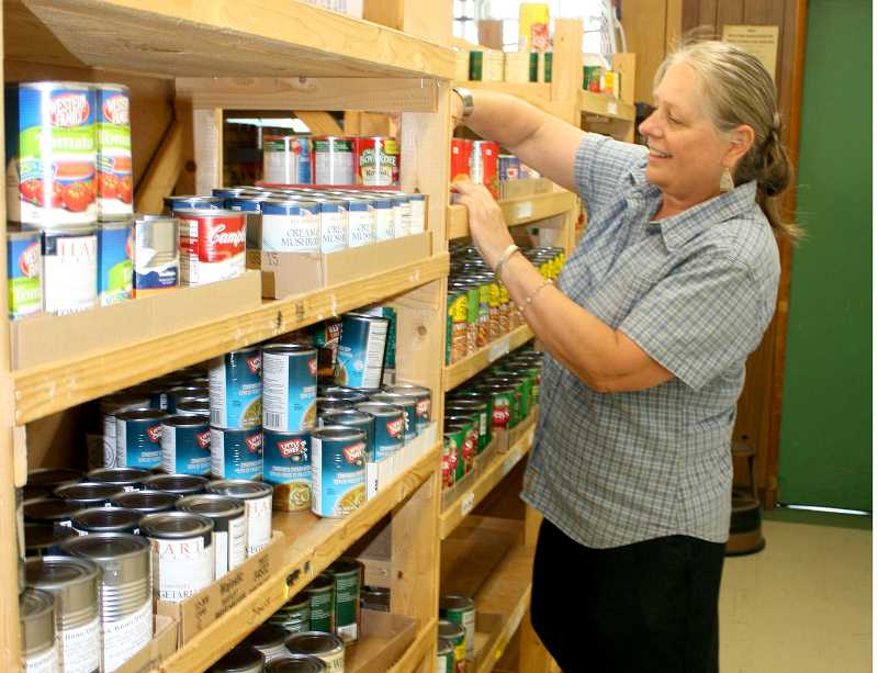 by: PEGGY SAVAGE - Molalla Service Center Director Rise Estergreen stocks shelves at the food bank.