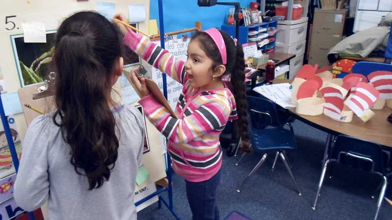 by: ROSA FLOYD - Daniela Hernandez discusses a project with a classmate in this photo taken last year when she was in kindergarten. This IB science project required students to research different frog species and share what they learned with the class.