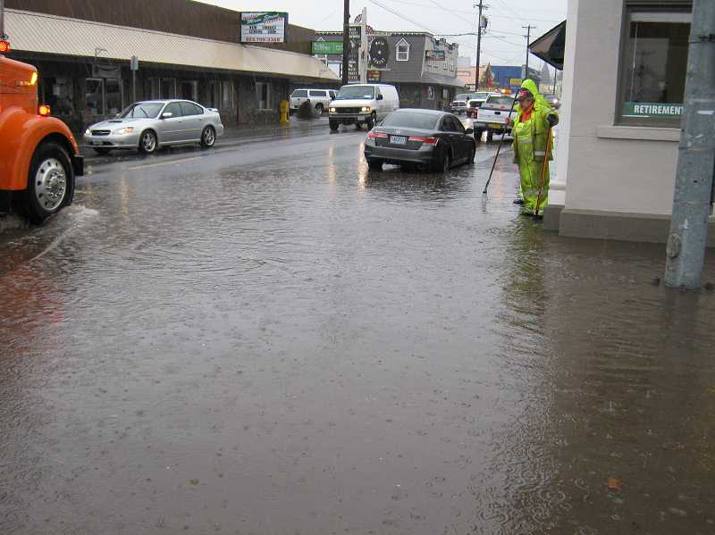 by: MPD OFFICER CURTIS THORMAN - city crews check out flooding at Molalla's main intersection Tuesday.