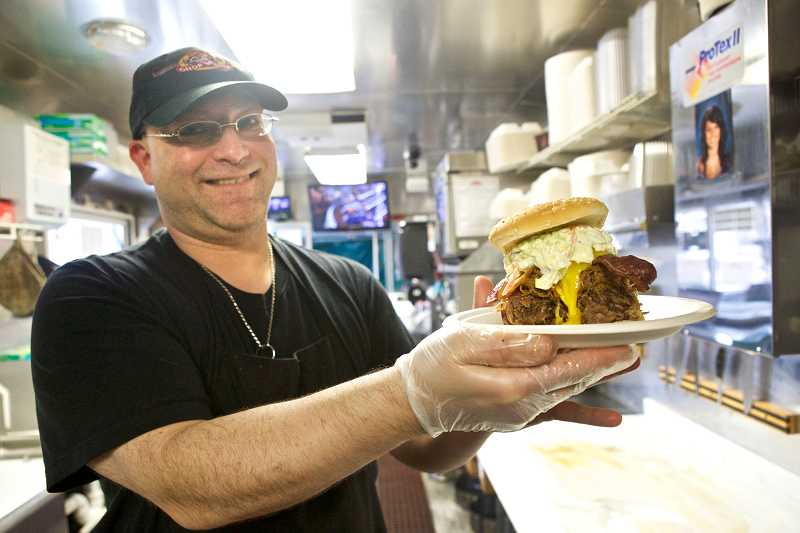 by: TIMES PHOTO: JAIME VALDEZ - Troy Herren, who is the manager and chef at Pork Chop City Smoke House, holds up a 'Totally Wrong' sandwich, which consists of smoked pulled pork, beef brisket, cheese, bacon and cole slaw.