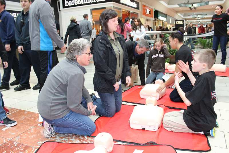 by: SUBMITTED PHOTO - Valley Catholic Middle School students Alex Moore, Alaina Hardy and Lara Spurgeon give shoppers the basics in CPR during a training session at Washington Square mall on Saturday