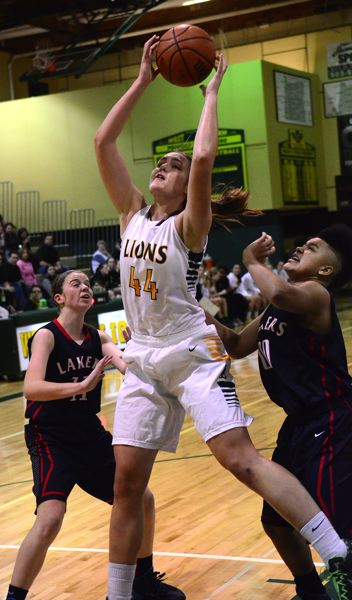 by: VERN UYETAKE - West Linn's Morgan Haskin rips down one of her 14 rebounds in West Linn's hard-fought win over Lake Oswego at home Tuesday.