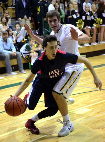 by: VERN UYETAKE - Lake Oswego guard Leo Spada drives past West Linn's Kevin Edwards during the Lakers' road game Tuesday.