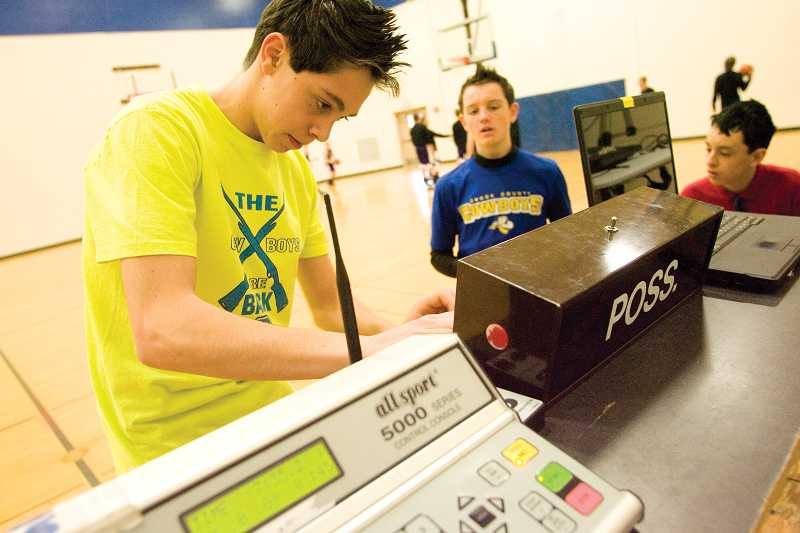 by: KEVIN SPERL - Jacob Mickel sets up the game clock before the start of a Crook County High School Freshman basketball game.