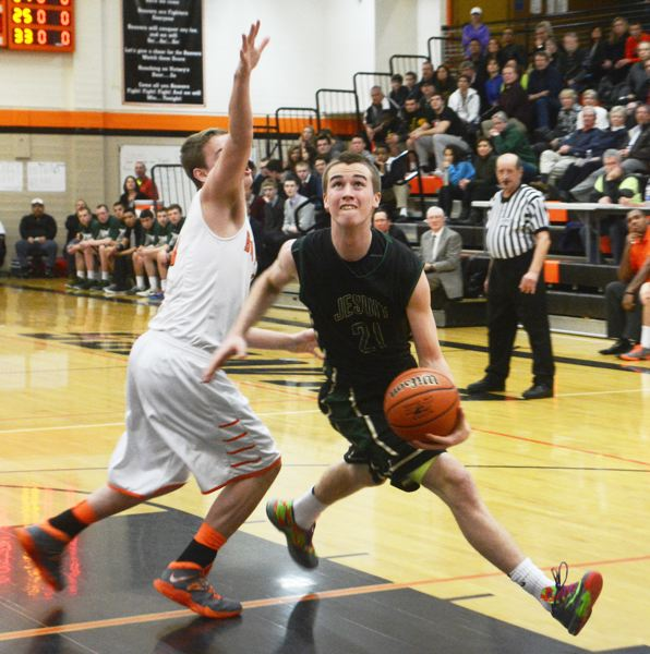 by: TIMES PHOTO: MATT SINGLEDECKER - Jesuit junior small forward Jack Nadelhoffer weaves across the lane for a lefty scoop against Beaverton.