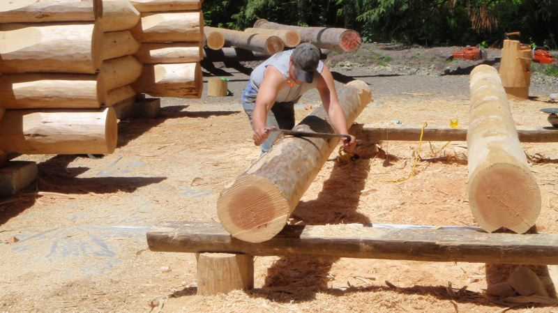 by: CONTRIBUTED PHOTO - Mark Fritchs employees often peel the logs by hand, creating very little noise for the neighboring lots.