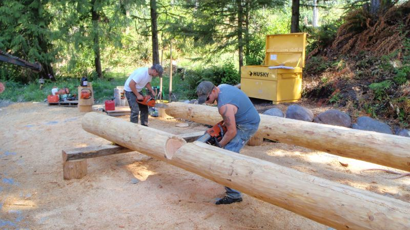 by: CONTRIBUTED PHOTO - The logs are notched and shaped on sit before being stacked into its future structure, a step that has been prohibited by a Clackamas County ruling.