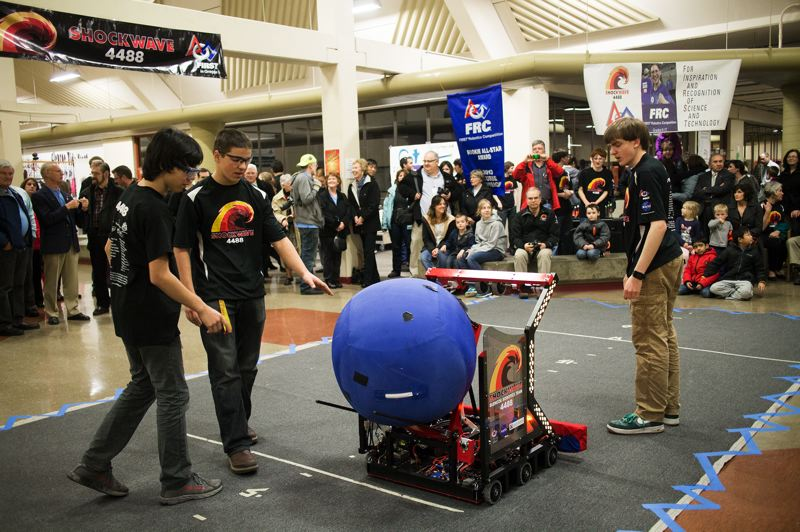 by: HILLSBORO TRIBUNE PHOTO: CHASE ALLGOOD - Members of Glencoe High Schools Team Shockwave load a ball into their robot.