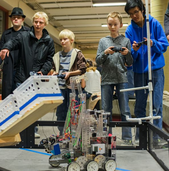 by: HILLSBORO TRIBUNE PHOTO: CHASE ALLGOOD - Nick Gill and Tin Huynh of Hillsboro High Schools Ultra Lightning Cobra Strike Force robotics team teach Luke McAllister and Peyton Miller how to operate their robots.