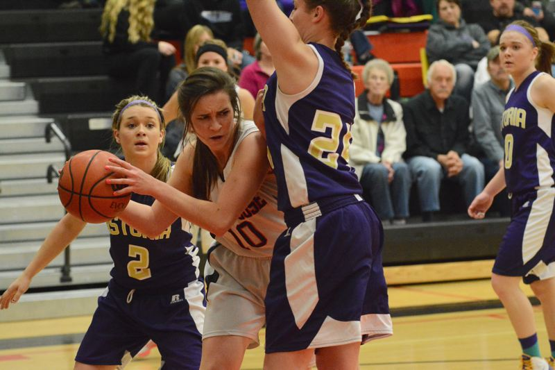 by: JOHN WILLIAM HOWARD - Abby Kessi looks to pass out of a double team after snagging one of her team-high nine rebounds during the Indians' win over Astoria.