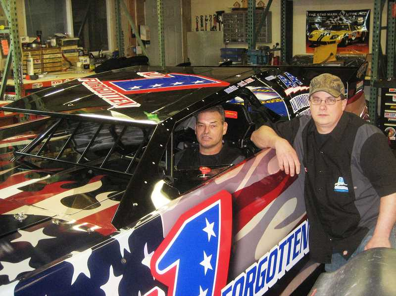 by: BILL MINTIENS - Rick Maul, co-owner of Prineville-based AA Automotive and Transmission Repair, sits inside the race car they are donating in honor of local veterans. Fellow co-owner Kelly Lawrence stands alongside the vehicle.