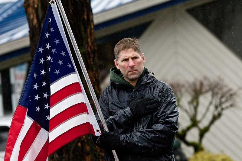 by: TIMES PHOTO: JAIME VALDEZ - Rich Clark of Beaverton shows his support for the Pelham family during the funeral procession for U.S. Army Spc. John A. Pelham.