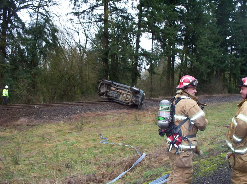 by: COLUMBIA RIVER FIRE & RESCUE COURTESY PHOTO - Firefighters respond to the scene of a wreck on Highway 30 Monday, Feb. 24, in Deer Island. A Toyota Tundra pickup truck, one of two vehicles involved in the crash, rolled over and came to a stop on the railroad tracks alongside the highway.