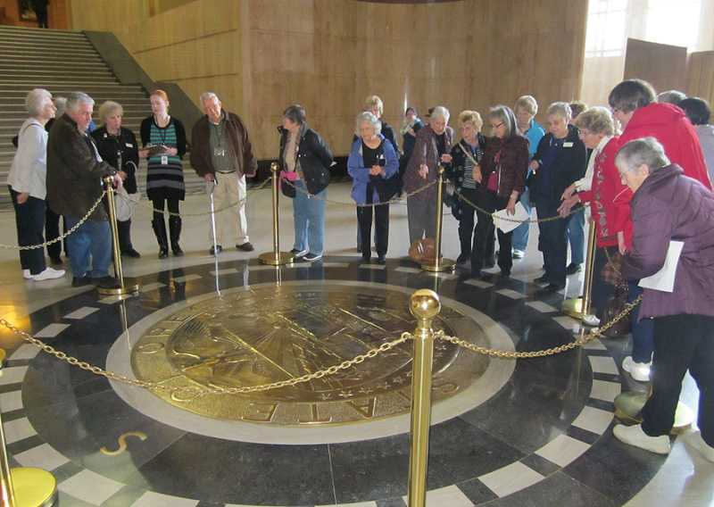 by: BARBARA SHERMAN - EXPLORING THE CAPITOL INSIDE AND OUT - Members of the King City Travel Club gather around the Oregon state seal in the Rotunda of the Capitol as a guide explains what the various symbols represent.