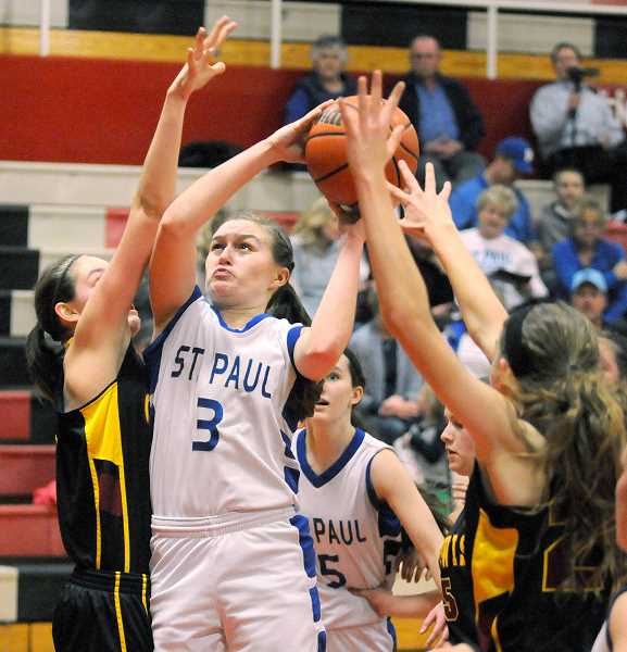 by: SETH GORDON - Lots of company - St. Paul senior Sara Pierson is flanked by two C.S. Lewis defenders as she makes a move to the hoop during the Bucks' 43-20 victory Saturday at McMinnville High School.