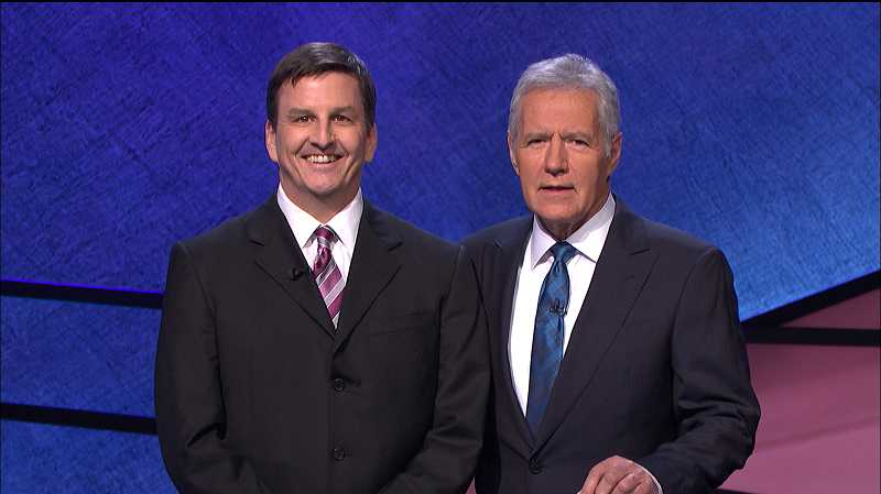 by: PHOTO COURTESY OF JEOPARDY! PRODUCTIONS, INC. - Ryan Fritz Holznagel (left), a Jeopardy! champion in 1994, has been invited back to Los Angeles to compete against three decades worth of winners, wholl be grilled by host Alex Trebek (right).