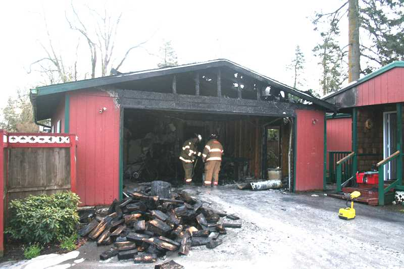 by: WOODBURN FIRE DISTRICT - Woodburn firefighters investigate the cause of an early Tuesday morning fire in West Woodburn.