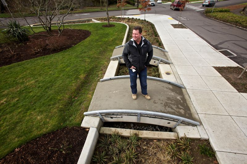 by: TRIBUNE PHOTO: JAIME VALDEZ - Bill Ryan, Bureau of Environmental Services chief engineer, says the agency uses green infrastructure projects only when they save money, and the environmental benefits are a bonus. Here he stands over a bioswale on a footbridge made from leftover pipe from the bureaus Big Pipe project that limited sewage discharges into the Willamette River.