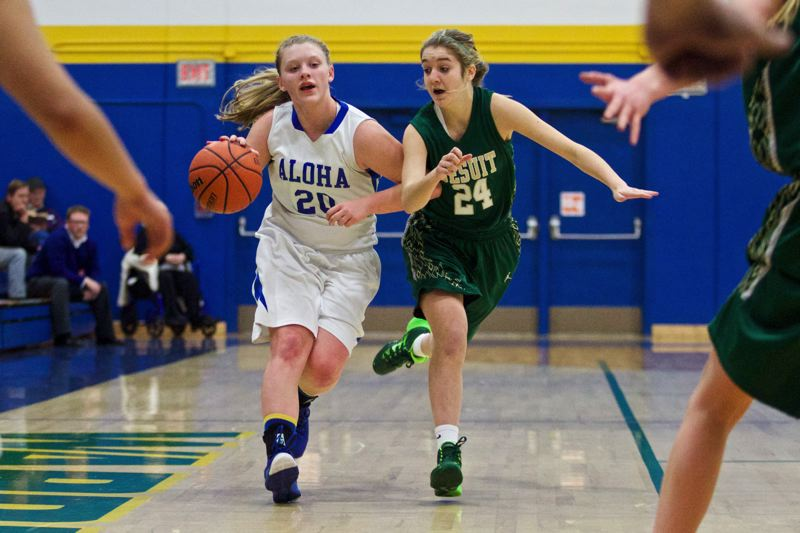 by: TIMES PHOTO: JAIME VALDEZ - Aloha Warriors guard Mackenzie Sibert (20) brings the ball up court against Jesuit Crusaders guard Lexi Barker (24) in the first half at Aloha High School.