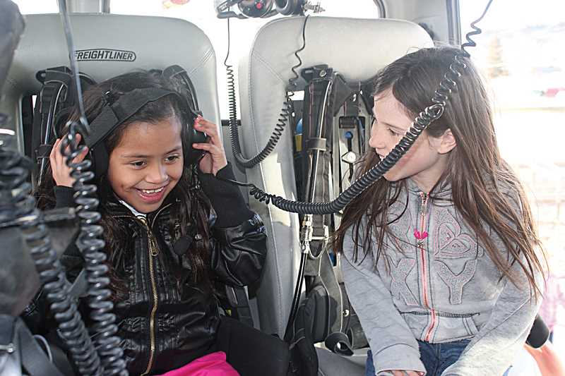 by: HOLLY GILL/MADRAS PIONEER - Arianna Flores, left, and Rianna Simmons try out headsets while touring the fire truck at the Kids Club Career Fair.
