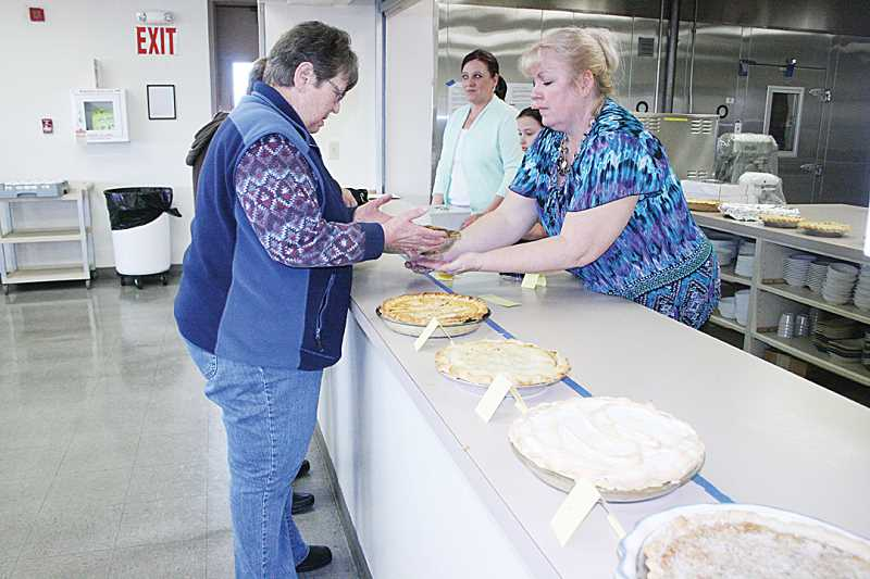 Pioneer ad manager Joy DeHaan, right, and Joey Lantz, at back, accept entries for the Madras Pioneer's Old-Fashioned Pie Contest, Feb. 22.