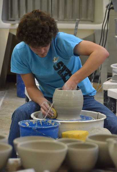 by: REVIEW PHOTO: VERN UYETAKE - Lakeridge senior Thomas Shearer throws some clay for Empty Bowls.