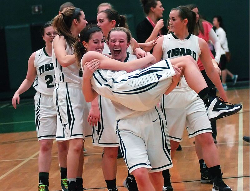 by: DAN BROOD - CARRIED AWAY -- Tigard High junior Kaylie Boschma gives Tiger senior Emilee Cincotta a lift off the court following Tigard's game with Forest Grove on Friday. Cincotta has 12 points and 11 steals in the 58-31 win.