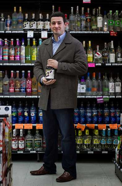 by: TIMES PHOTO: JONATHAN HOUSE - Chris Joseph of Wild Roots Vodka with his top-shelf, infused vodka at the Beaverton Liquor Store. He plans on moving much of the production from Bend back to Beaverton.