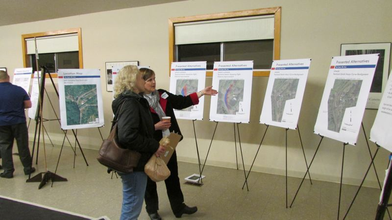 by: MARK MILLER - Sandy Prock, project manager for an ongoing effort to design safety improvements on Northwest Cornelius Pass Road in Multnomah County, converses with an open house attendee at the Skyline Grange Tuesday, Feb. 18. Prock, center-right, was one of several Multnomah County employees on hand to speak with the public at the event.