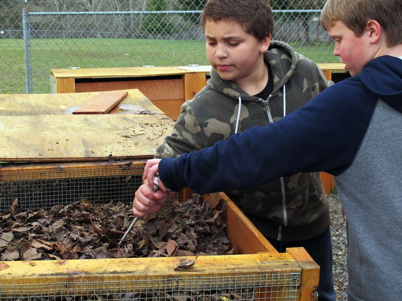 by: HILLSBORO TRIBUNE PHOTOS: KATHY FULLER - Eric Sanchez and Brady Job check the temperature of the compost bin at Tobias Elementary School.