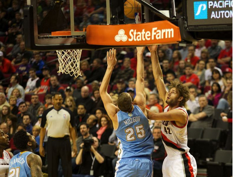 by: TRIBUNE PHOTO: JAIME VALDEZ - Trail Blazers center Robin Lopez shoots over Denver Nuggets center Timofey Mozgov during Saturday night's game at Moda Center.