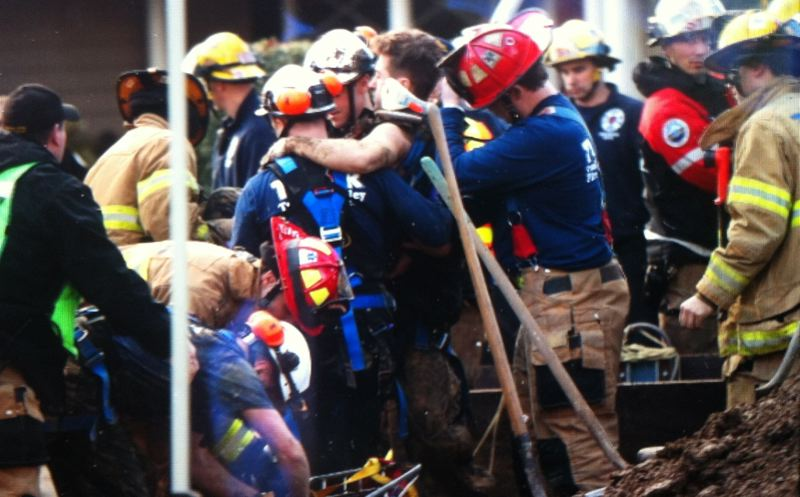 by: VALLEY TIMES PHOTO: JAIME VALDEZ - Crews from Tualatin Valley Fire & Rescue and Portland Fire & Rescue helped free a man trapped Monday morning when a 15-foot trench collapsed in the Cedar Hills area.