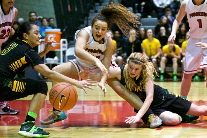by: JAMIE VALDEZ - Oregon City sophomore post Taylor Shaw (center) battles Caitlin Malvar (left) and Morgan Haskin for a loose ball in last weeks pay-back win over the West Linn Lions.