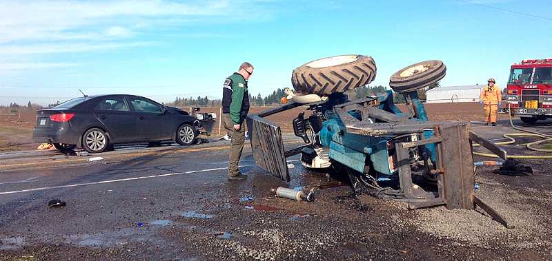 by: RAY HUGHEY - A Clackamas County Sheriff's deputy checks the damage at the accident scene Friday.