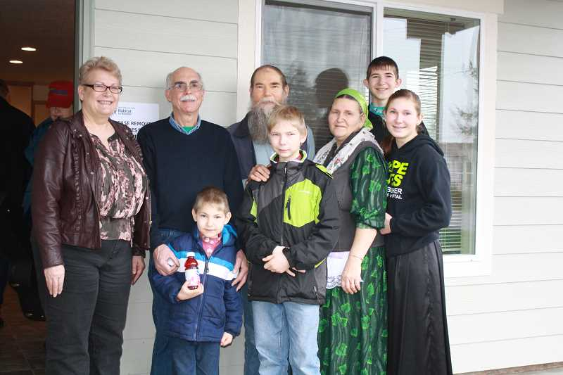 by: BETH FAULHABER - The Snegirev family poses in front of their house with Habitat staff LouJean Fobert and Tom Mason (left and second from left).