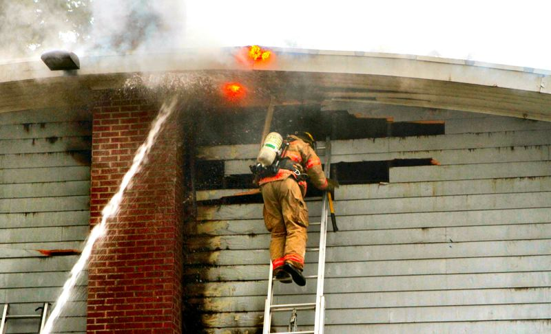by: DAVID F. ASHTON - As fire breaks through the eaves, firefighters below hit the flames with a water stream, protecting the crew member working high on a ladder.