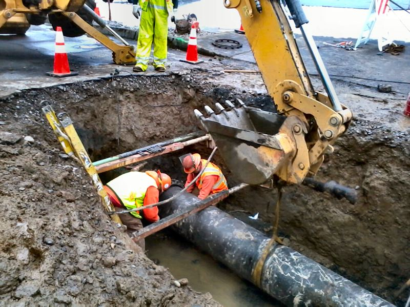 by: COURTESY OF PORTLAND WATER BUREAU - It didnt take long for Portland Water Bureau workers to get down to business, locating and fixing the broken cast iron water main - buried several feet under the road.