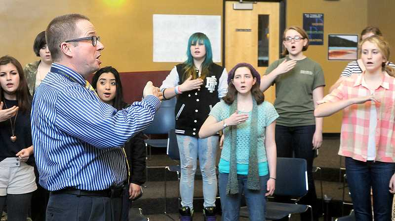 by: GARY ALLEN - Flexing their vocal chords -- Choir director Robert Hawthorne works with students Friday afternoon at Newberg High School.