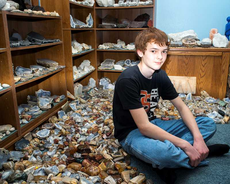 by: NEWS-TIMES PHOTOS: CHASE ALLGOOD - Thirteen-year-old Brian True sits amid one part of his 10-ton rock collection in his Cornelius home. He will help at the clubs annual rock and gem show this weekend at the Washington County Fairgrounds.